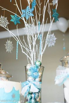 Frozen birthday centerpiece!! Looks easy to make.. I'd use dollar store hurricane glass and spray paint branches from outside & find cheap ornaments at Walmart!!!