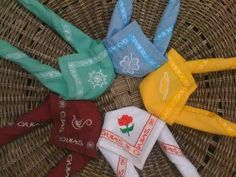 Neckerchiefs for each section of the  Asociación Guías Argentinas. Rainbows are white, Brownies are yellow, Junior Guides are blue, senior Guides are aqua, Ranger Guides are maroon.
