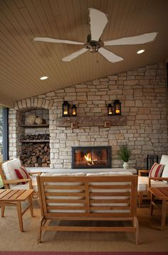 Beyond the family room is this unique screened-in porch. The stone facing is buechel, quarried in nearby Wisconsin. The rustic mantel is a reclaimed barn beam. Another subtle arched detail houses logs and other fireplace supplies.