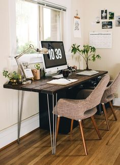 Your home office should inspire creativity. This large dark wooden desk allows two people to sit at it, making it perfect for meetings and presentations. The plants next to the desk and the colour of the stationary highlight the very natural feel this office creates.