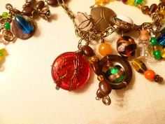 On the left is a shell button with a blue bead wired on. The red 'charm' is a small rosary case. Next to it is a brown beer bottle top with added beads. The tiny bottle has watch gears inside that I got from an old watch.