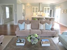 i like the layout of this living room table in th middle and couch on one side with chairs on either side.
