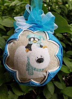 Polar fun is a quilted handmade keepsake ornament. Petey Penguin catches a ride on a friendly polar bear for a day of ice fishing. Topped with a blue and white bow.