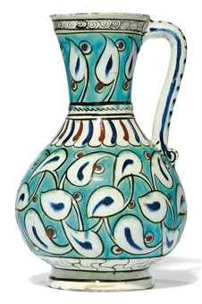 AN IZNIK POTTERY JUG, OTTOMAN TURKEY, CIRCA 1570 - Of baluster form on short foot rising to flaring trumpet mouth & with simple loop handle, decorated in turquoise, cobalt-blue, bole-red & black, the body with allover design of scrolling arabesques issuing white & blue fleshy lobed leaves reserved on a turquoise ground, the neck with similar register of single leaves curling to the left, the base with a band of stylised marbling... 9¾in.  high