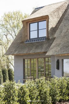 Een rieten dak, je houdt ervan of niet. Maar als kroon op een hedendaagse woning – uitgepuurd, charmant en een tikkeltje exotisch tegelijk – kan je niet anders dan ervan houden. De woning verenigt het karakteristieke dak met hedendaagse architectuur. Een combinatie die wonderwel werkt door de verbindende materialenkeuze. Style At Home, Home Interior Design, Interior And Exterior, Villas, Wood Facade, Thatched Roof, House Windows, Toscana, Dream Decor