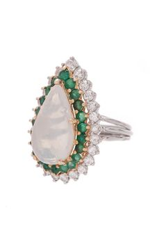 Speak profoundly of ladylike luxury with this authentic 18K gold and platinum ring. In this vintage piece, a stunning pear shaped cabochon cut opal gemstone is bordered by elegant emeralds and dazzling diamond accents. Requiring little in terms of additional accessorizing, this radiant ring was designed with statement-making intentions.