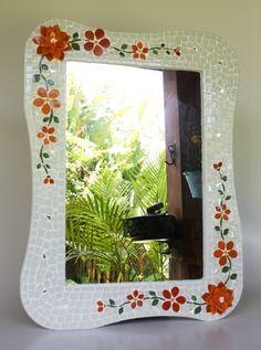 Além de serem úteis, os espelhos exercem um papel importante na decoração de qualquer ambiente: ilumina, amplia e alegra salas, lavabos, quartos, varandas, halls, entradas de apartamentos, escritórios, consultórios... <br> <br>Esse espelho em mosaico foi confeccionado em pastilhas de vidro formando flores em tons de laranja e ramos e folhas verdes. O detalhe desse espelho é que duas flores são em alto relevo, dando um charme a mais ao mosaico. A moldura é em mdf. <br>A parte interna do ...