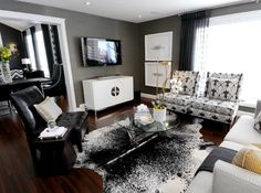 Chic modern living space with pops of yellow. Gray grasscloth wallpaper, Jonathan Adler Channing Buffet in White Lacquer, white & black cowhide rug, modern wingback chairs upholstered in Kelly Wearstler Bengal Bazaar Fabric in Graphite, oatmeal linen sofa with nailhead trim,