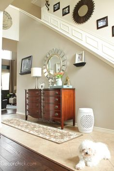 Love the use of a dresser in the entry way. Notice the Chinese white ceramic seat instead of a plant softens the edges