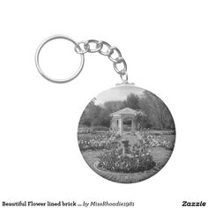Beautiful Flower lined brick walkway in garden Basic Round Button Keychain  Displaying style and class, beautiful flower lined brick walkway in garden is a reminder of how beautiful nature can be. Set in a garden, this black and white photo showcases lovely flowers of all varieties. Add to your cart today!  #keychains #flowers