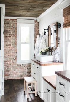 This vintage inspired farmhouse bathroom is ready for spring and summer! Love this brick wall in farmhouse bathroom and wood ceiling - and those butcher block countertops!