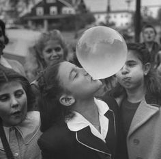 A young girl blowing a large bubble gum bubble, 1946