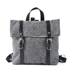 A stylish and practical backpack in classic grey herringbone Harris Tweed and waxed cotton. Fully lined interior in natural linen with an additional waterproof interlayer. The bag has a black waxed cotton back with a full-width zipped pocket. Foldover top closure secured with two black, vegetable-tanned leather buckled straps. Adjustable shoulder straps and top carry handle in black heavy cotton webbing. Designed by Catherine Aitken and handmade in Scotland.