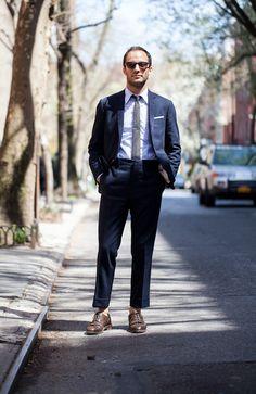 Shop this look on Lookastic:  https://lookastic.com/men/looks/suit-dress-shirt-brogues-tie-pocket-square-sunglasses/9416  — Dark Brown Sunglasses  — Light Violet Vertical Striped Dress Shirt  — Grey Plaid Tie  — White Pocket Square  — Navy Suit  — Dark Brown Leather Brogues