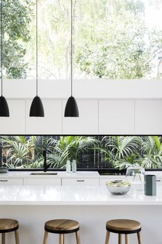 Stunning contemporary kitchen with large picture window behind sink and as kitchen splash back. Matte black hanging pendant lights. Green wall of planting.