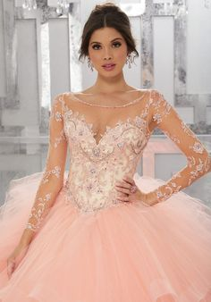 This Gorgeous Quinceañera Ballgown Features a Beaded and Embroidered Bodice Accented with an Illusion Neckline and Long Illusion Sleeves. Matching Stole Included. Colors Available: Capri, Black Cherry, Champagne/Blush, White.