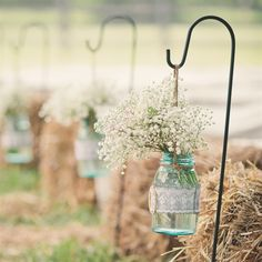 Along the aisle were antique Ball jars, wrapped in lace and grey burlap with a gold and diamond buckle.