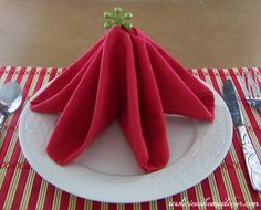 How to fold a napkin into a Christmas tree tutorial How Easy Christmas Tree Napkin Tutorial.  It will complete any table setting for the holidays! sewlicioushomedecor.com #napkins