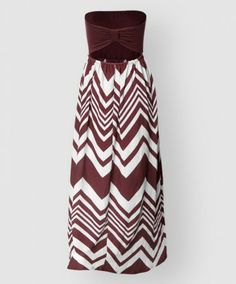 This ultra soft and flowy maxi dress is perfect for gameday or class. Made of a cotton elastic blend the material moves and stretches. The bodice is maroon and the bottom is a maroon and white chevron pattern. The back of the bodice is gathered together and has a back keyhole.