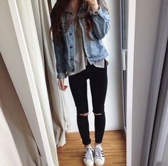 Wavy hair, grey tee, denim jacket, black jeans and grey trainers.