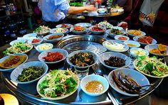 Table setting around a Korean BBQ grill. To meet standards, the many complimentary side dishes (Banchan 반찬, varies by location & restaurant) arrives before the main food! [PHOTO]