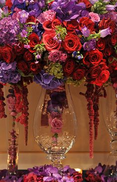 Wow... there is a centrepiece.. Notice that the artist has carefully designed the vase inside. Love the colours of red, purple, pink, and green roses  Cena de Navidad: Centros de Mesa | Inspirations