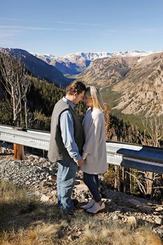 Fall Engagement Session - Outdoor - Red Lodge - Montana - Beartooth Pass - Overlook - Engaged Couple - Fiancé - Man - Woman - Mountains - Trees - Snow - Blue Sky - Rocks - Railing - Head to Head - Jeans - Jeggings - White Boots - White Sweater - Blue Denim Shirt - Carhartt Vest - Montana Wedding Photographer - Sara Nagel Photography