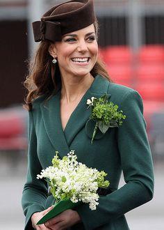 Catalina de Inglaterra con un 'look' otoñal, combinando abrigo verde y tocado con un pequeño ramo blanco.