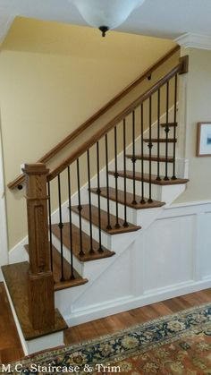 Staircase remodel from M.C. Staircase & Trim. Removal of old treads, wooden balusters, handrail and newel post. Installation of starting step, treads, risers, flat paneled newel post, handrail, square rosettes and iron balusters. Iron balusters are the Versatile Plain bar and Single Knuckle in Satin Black.
