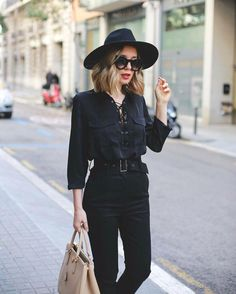 A lace-up top, black skinny trousers, a fedora, and sunglasses.