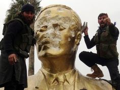 Fighters loyal to Jabhat al-Nusra and its allies smash a statue of Hafez al-Assad in the Syrian city of Idlib.