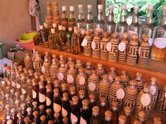 A stand of Lao Lao (or Mekong Whiskey made from sticky rice) in  Whiskey Village (Ban Xang Hai), Laos. If you look at the bottle on the upper right, you'll notice they contain snakes with scorpions in their mouths. Taken by Talmadge O'Neill