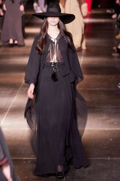 Black chic witch.  Elegant drape skirt with draped long sleeved shirt. Open center front. Witch hat to complete the look. #PFW #SP2013