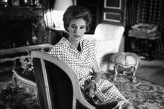 Babe Paley, photographed in her St. Regis drawing room, wears Givenchy's black and White Hexagonal silk print with two twisted black and white, pearl bracelets and a black and white pearl ring, 1963.