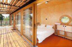 These rooms in a shipping container hotel have walls and ceilings made from plywood.