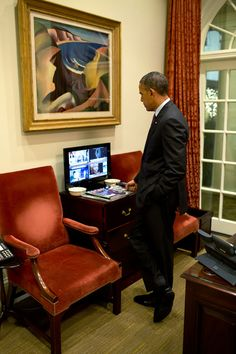 2013: The President watches news coverage of the passing of Nelson Mandela, in the Outer Oval Office.
