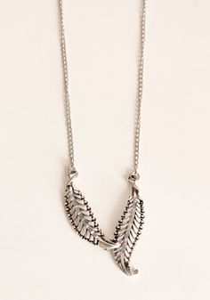 To the Horizon Feather Necklace $14.00   Silver colored necklace with 2 feather pendants connected at their tips, all on a long chain.