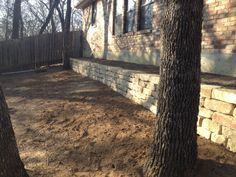 Groundscape, a Fort Worth Landscape Company, installs a dry stacked retaining wall with native sandstone builders.