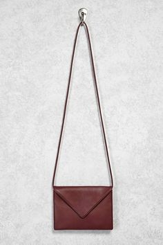 An unstructured mini faux leather crossbody bag featuring an envelope flap, a hidden snap-button closure, and a skinny shoulder strap.