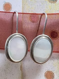 """Sterling silver pierced earrings with silky white mother of pearl stones. Stones have a nice pastel color flash. Marked 925. Measure 1 1/8"""" by 1/2"""" wide. Total"""