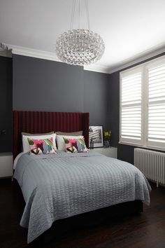 Add instant elegance to your bedroom with dark gray walls. It's a terrific choice for showing off decorative white-painted trim because of the contrast it provides. Of course, a dark hue can eat up a lot of light in the space and look a little flat. Counteract that by adding sparkling elements to the room, such as the stunning chandelier seen here.