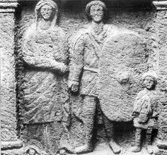 Боспорская надгробная стела Родона, сына Гелиоса, начало I в. н.э. Отец семейства изображен в короткой тунике, штанах плаще, застегнутом на правом плече. В руке он держит большой овальный щит с небольшим умбоном. Сын держит шлем. Различимы вертикальные полосы и височные пластины.