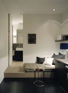 clean monochromatic bedroom with a platform bed area step up into the bathroom suite.
