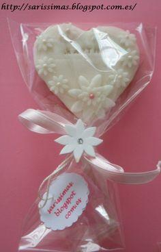 Galleta en forma de corazón decorada con pasta de azúcar y flores pequeñitas y una más grande con puntito de color rosa.