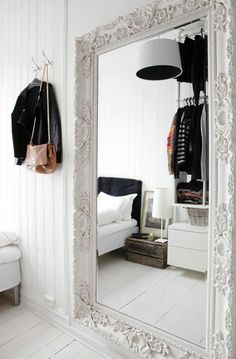 Love this oversized ornate white mirror which enlarges the space n this white room.  #whitemirror #whitehardwoodfloor #whitepaneling