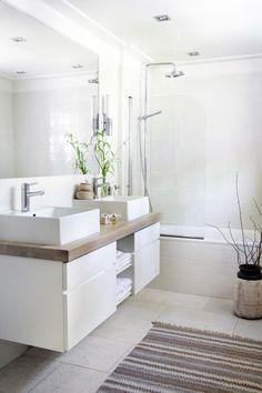 es el cuarto de baño. Es muy sencillo con el color blaco. Tiene dos fregaderos y una ducha.
