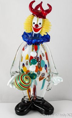 The Murano Glass Clown stands holding a bright ball with an unusual Jester hat with four peaks