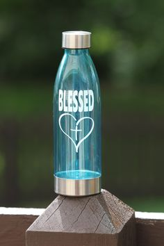 Graphics include BLESSED with cross inside heart. Hydration for cold drinks with 22 oz capacity. The bottom of bottle is protected with layer of stainless steel. Standard ice cube fits through over-sized bottle opening. Gym Water Bottle, Cute Water Bottles, Water Bottle Holders, Steel Water Bottle, Water Bottle Design, Diy Vinyl Projects, Bottom Of The Bottle, Glitter Cups, Bottle Necklace