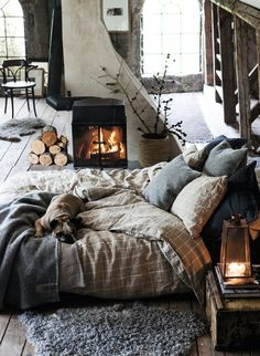 Ultra comfy bed on floor with rustic fireplace