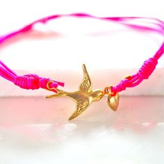 Swallow and Heart Friendship Bracelet The detailed swallow and heart is tied on a neon pink strong nylon cord finished with gold plated crimps and sliding knots. £12.00